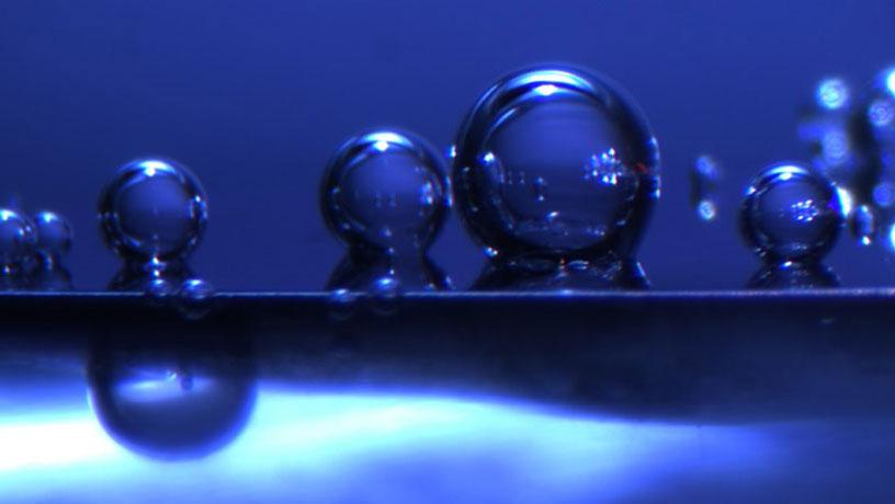 In-situ photo of hydrogen bubbles against a blue background.