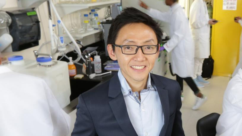Portrait of Prof. Ngai Yin Yip in the lab with researchers in the background.