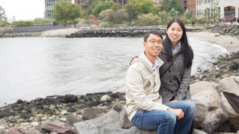 Nicholas Chack and Connie Qiu sitting by the river in Brooklyn.