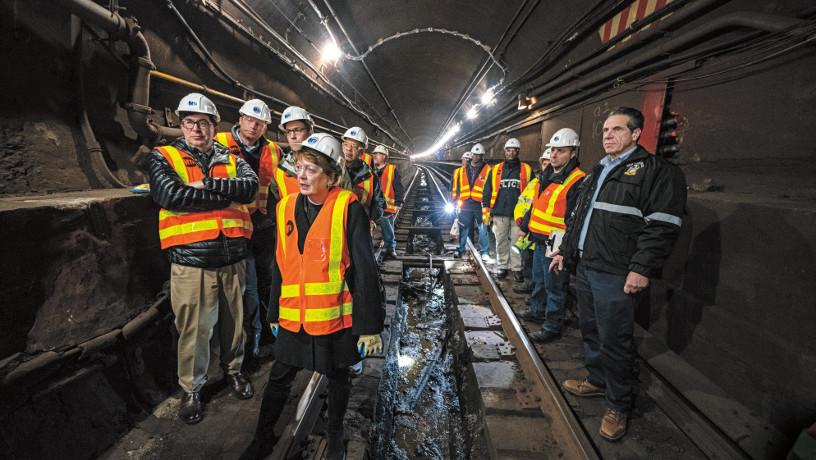 A group of experts inspect the L train tunnel with Dean Mary C. Boyce and Gov. Andrew Cuomo in the foreground.