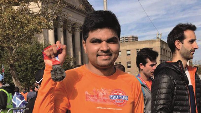 Pranay Dharmale holding a medal after a race.