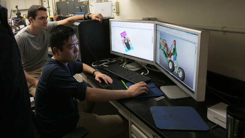 Two students reviewing the CAD model of the race car on computers.