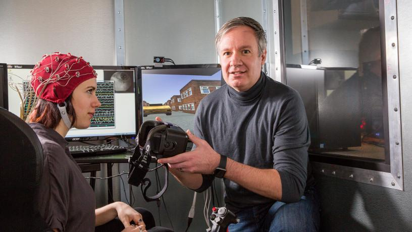 Prof. Paul Sajda holding VR glasses in his lab with research assistant Jennifer Cummings wearing electrodes.