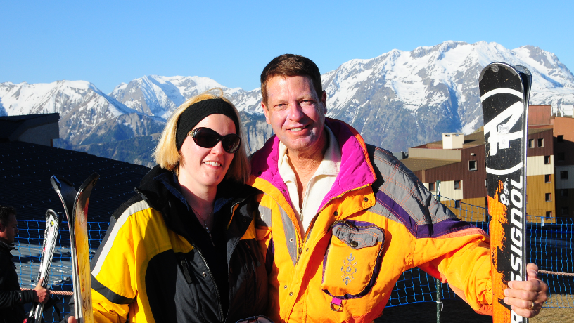 Yoseph Melman and wife during a ski trip with mountain in the background.